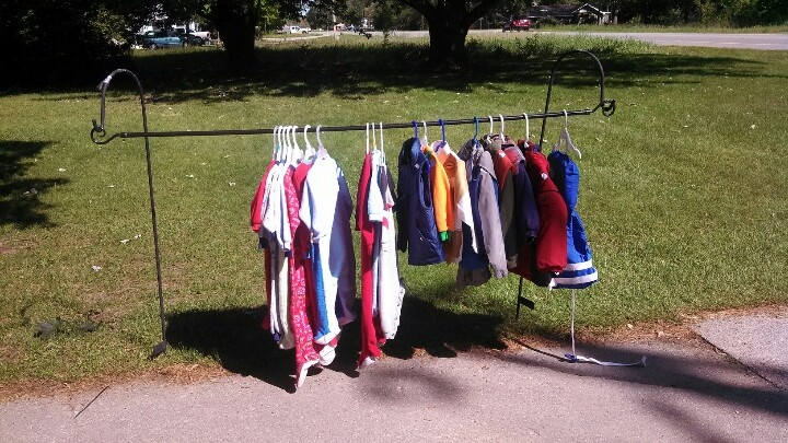 Creative way to hang clothes at a yardsale. Two shepard hooks and a curtain rod!