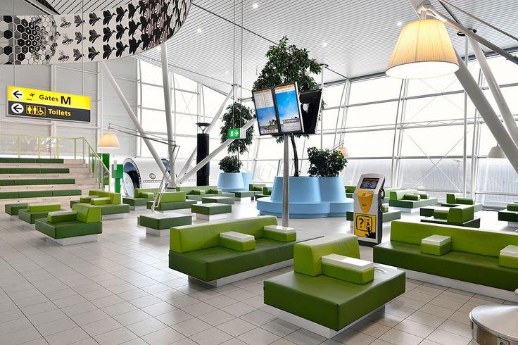 """De winkels en horecagelegenheden in de Lounge 4 zijn voorzien van sterk variërende gevels, met grote entrees. De wachtruimte zelf is voorgesteld als een """"graslandschap"""", met royale groene Lensvelt-banken naar ontwerp van Joep van Lieshout."""