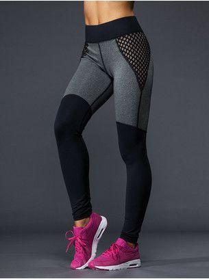 Elle porte des pantalons de jogging noirs et gris, et des baskets roses.