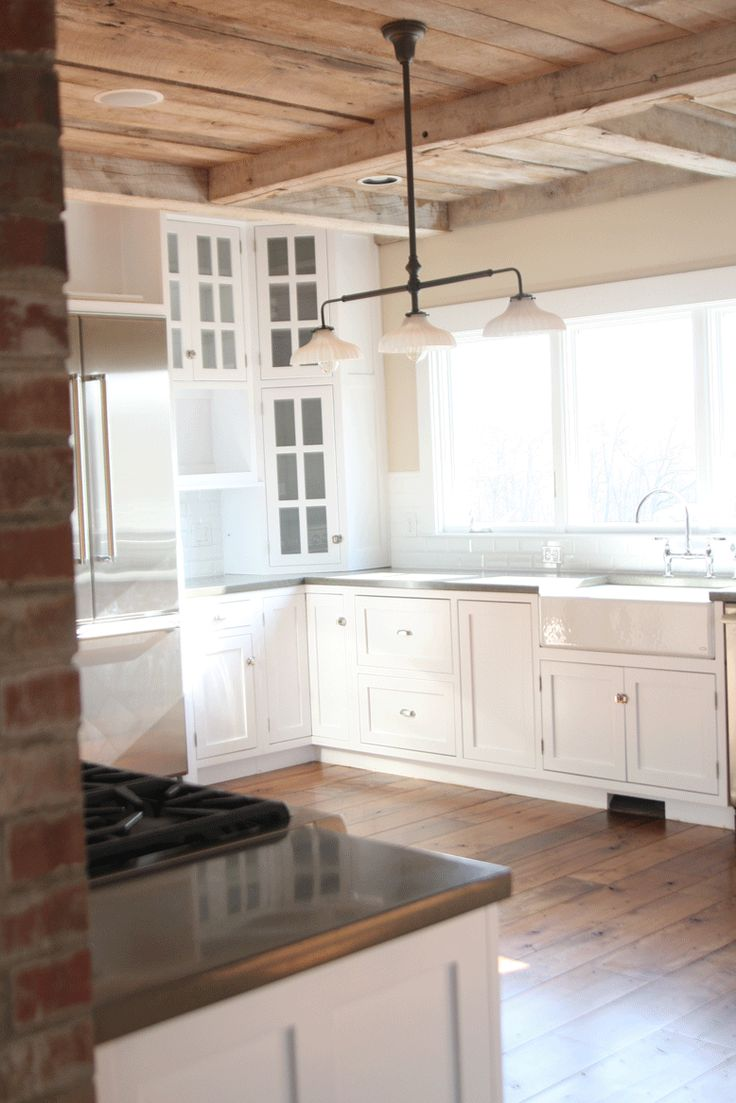 on the opposite side of the fireplace is the stove, in this farmhouse kitchen