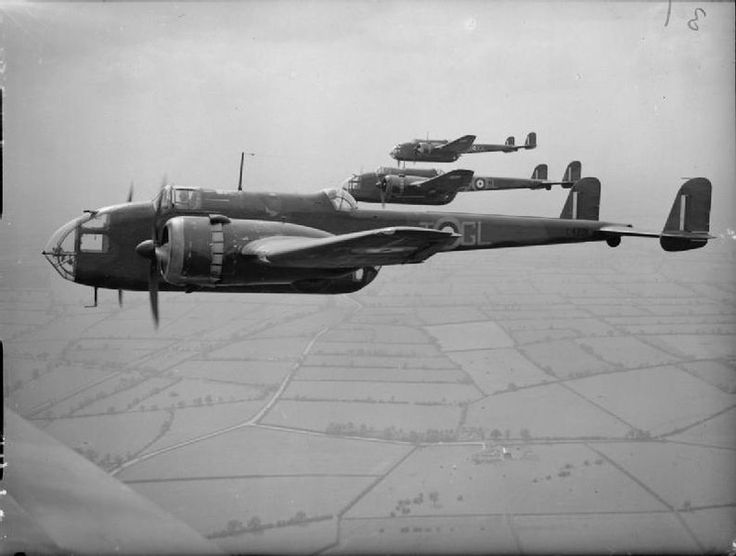 Three Hampden Mark Is of No. 14 Operational Training Unit based at Cottesmore, Rutland, flying in echelon formation over the countryside. These aircraft still carry the unit code letters GL of No. 185 Squadron RAF which disbanded and merged with 14 OTU on 8 April 1940.