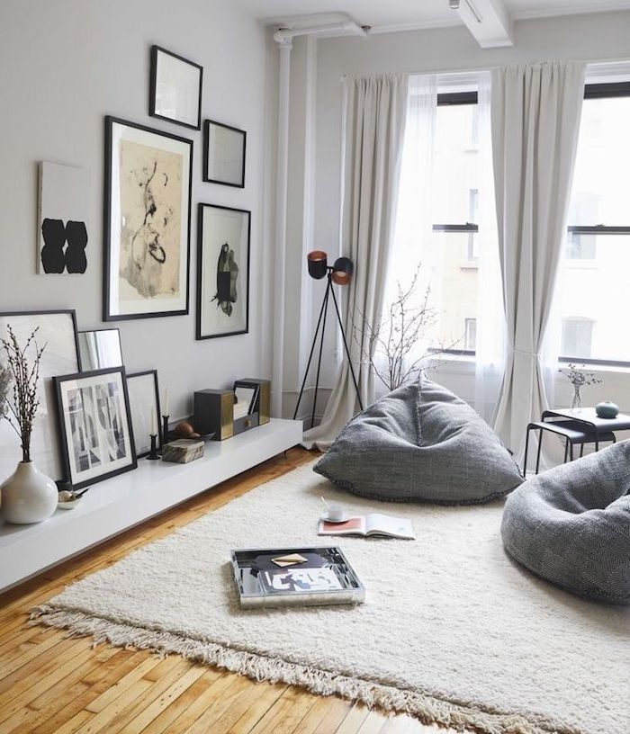 deco salon gris, fauteuils gris, tapis blanc cassé, parquet clair, mur couleur blanche, deco murale de dessins graphiques