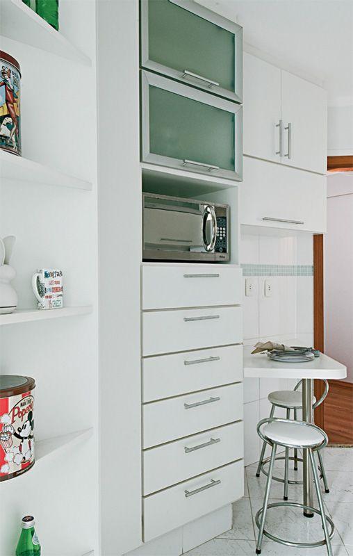"""Somam-se ao gabinete da pia e aos módulos suspensos, a torre do chão ao teto e cantoneira, além de uma bancada de refeições para dois. """"Com tanto espaço, consigo deixar tudo bem organizado"""", diz Débora."""