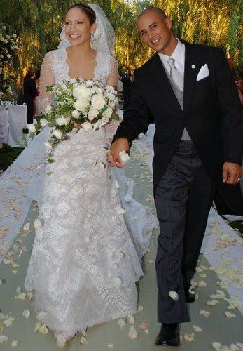 Jennifer Lopez married her former backup dancer, Chris Judd, on September 29, 2001. The bride wore an off-white silk and Chantilly lace A-line gown, with a low scoop neckline and sheer sleeves by Valentino Couture. All seven bridesmaids also wore Valentino. Their wedding ceremony was held at a mountaintop private home in Calabasas, California. A truck transported 10,000 pastel rosebuds to the suburban home for the lavish wedding. They divorced in January 2003.