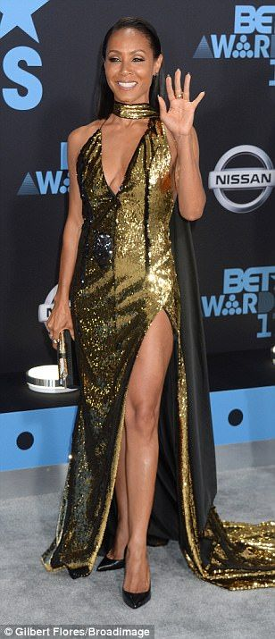 Gold standard! Jada Pinkett Smith dazzled in a glittering gold gown with plunging neckline...