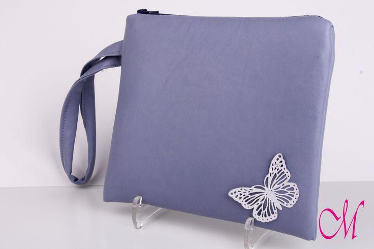 Bolso de mano en napa azul con cierre de cremallera y agarre lateral y decorado con una mariposa. www.monetatelier.com