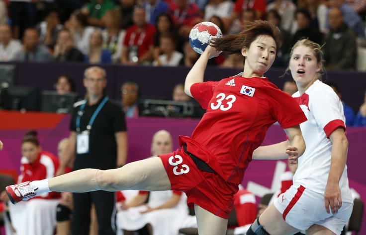 Lee Eun-bi of South Korea, left, takes a shot at goal as Marianne Bonde Petersen, right, of Denmark watches during their women's handball preliminary match at the 2012 Summer Olympics, Monday, July 30, 2012, in London. (AP Photo/Vadim Ghirda)