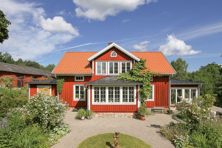 Framsidan av huset med fin grusad rundel. Huset har tre tillbyggda delar, till…