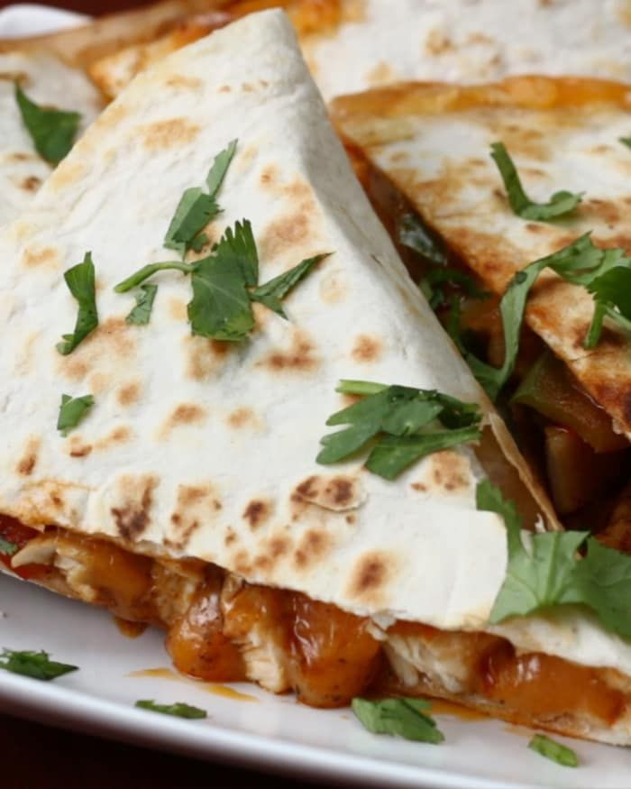 Servings: 2 quesadillasINGREDIENTS½ pound chicken breast, cut into thin strips½ teaspoon salt½ teaspoon pepper½ tablespoon chili powder½ teaspoon cumin¼ teaspoon cayenne¼ teaspoon garlic powder½ cup green/red/yellow bell pepper, julienned½ cup white onion, julienned2 large flour tortillas1 cup cheddar cheese, shredded (double for 2 quesadillas)1 cup monterey jack cheese, shredded (double for 2 quesadillas)GARNISHCilantroGuacamoleSour CreamPREPARATION1. In a large skillet, coat chicken with…