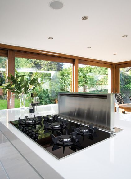 Contemporary Kitchen by Glenvale Kitchens   Downdraft extractor   It rises up out of the worktop when in use, but sits completely flush with the surface when not. Often installed to the side or behind the hob (as seen here), downdraft hoods work on the theory that the closer you place the extractor to the source of cooking, the more chance you have of successful extraction before the 'dirty' air can disperse around the room.