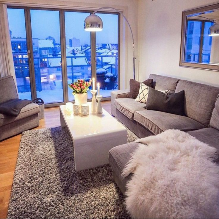 Grey & white living room - the coffee table and standing light. Also notice the lounge decor and ottoman's arrangement