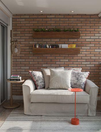 Varanda com parede de tijolo e cores claras para o merecido descanso! Os nichos em madeira e a luminária descolada apoiam os livros no canto de leitura. Mesa Jardim de Jader Almeida em laca laranja dá o toque de cor!
