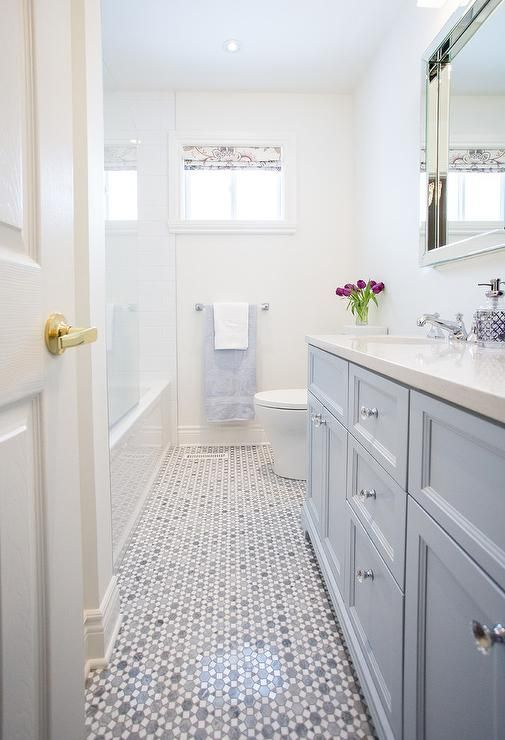 Long bathroom features a blue dual vanity topped with a white quartz countertop which mimics white marble under individual beveled vanity mirrors facing a water closet next to a drop-in tub finished with a partial glass shower partition alongside a gray marble geometric tiled floor, Saltillo Imports Large Sunflower Carrara Thassos Tiles.