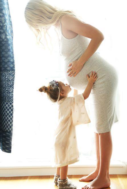 Preciosa fotografía de madre embarazada con su hija. Niña besando la tripa de su mamá embarazada