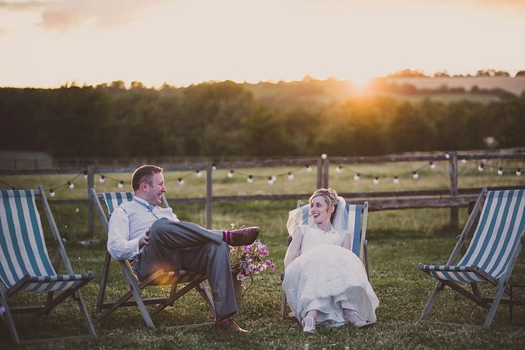 Image by - Lola Rose Photography - Bride & Groom Relaxing on deck chairs in the countryside - Sottero & Midgely Lace Wedding Dress and Rachel Simpson Shoes for a rustic country wedding in a barn with delicate pastel flowers. Bridesmaids in Navy & Groom in Grey Bartlett and Butcher Suit.