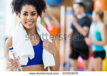 Fit woman smiling at camera at the gym - stock photo