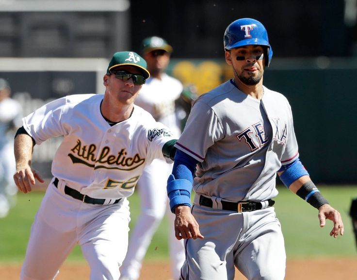 Robinson Chirinos is tagged out by A's second baseman Joey Wendle on a rundown between second and third on a ground ball from Hanser Alberto in the second inning Saturday, Sept. 24, 2016, in Oakland. (AP Photo/Marcio Jose Sanchez)