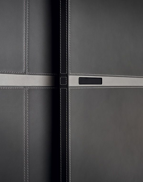 Detail of Bangkok wardrobe coplanar door covered in grigio hide with stitching. Central crossbar piombo mat lacquered with built-in handle.