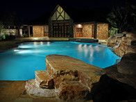 """Rather than a traditional diving board, the owner of this Mississippi pool opted for a """"jump rock"""" made from stone steps, for plunging into the pool, which ranges from 36"""" to 10' deep. Natural boulders form the back of the pool, and a spa area off the master bedroom features an outdoor shower designed like a natu"""