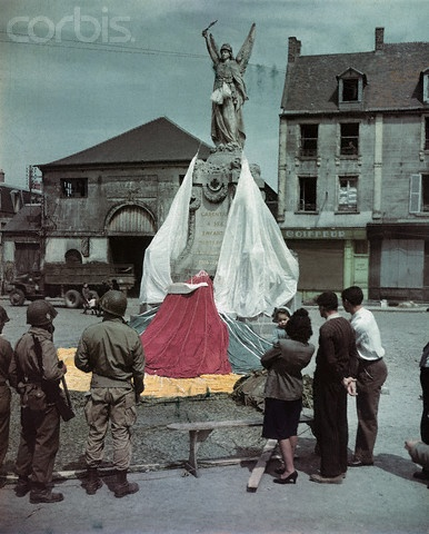 Memorial Decorated with Parachutes - U00986ACME - Rights Managed - Stock Photo - Corbis. Yank 'chutes decorate French memorial. Carentan, France: American soldiers and French civilians admire that memorial to World War I dead in Carentan fancifully decorated with varicolored parachutes dropped near the town the night before D-Day. A mother and her child ignore the statue to gaze at the living symbols of freedom embodied in the Yank airborne soldiers part of the force that liberated Carentan.