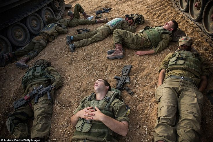 Israeli soldiers sleep next to armored personnel carriers near the Israeli-Gaza border on ...