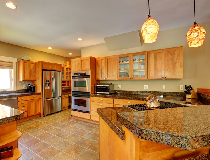 This large kitchen has tons of countertop space, stainless steel appliances, granite countertops and glass pendant lighting above the eat-in bar.
