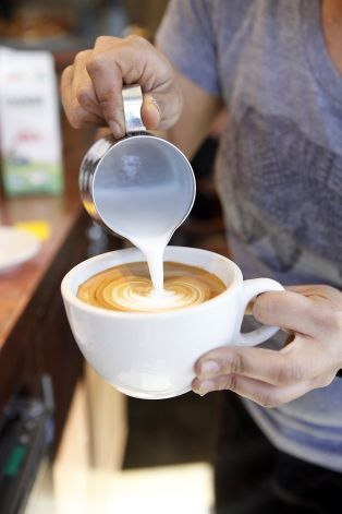 Barista Cat Mungcal pours designs into latte foam while working at Equator Coffees at Proof Lab Surf Shop in Mill Valley, CA...