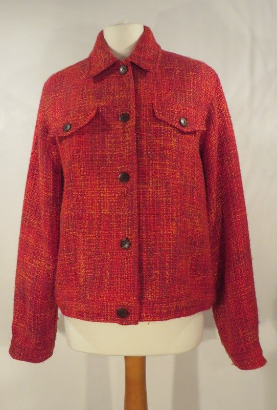 Vintage red boucle jacket, 14.   Stylish wool boucle jacket in red, interwoven with orange and maroon. Fully lined with very dark brown flecked buttons which also feature on the faux breast pockets and cuffs. The bottom is trimmed with a band which could add a slightly more casual feel - it would look terrific with jeans!   Size: 14 Measurements: B: 44, W: 44, H: 44, L: 23, S-S: 17 Label: None Decade: 1970 Material: Wool Cleaning instructions: Dry clean