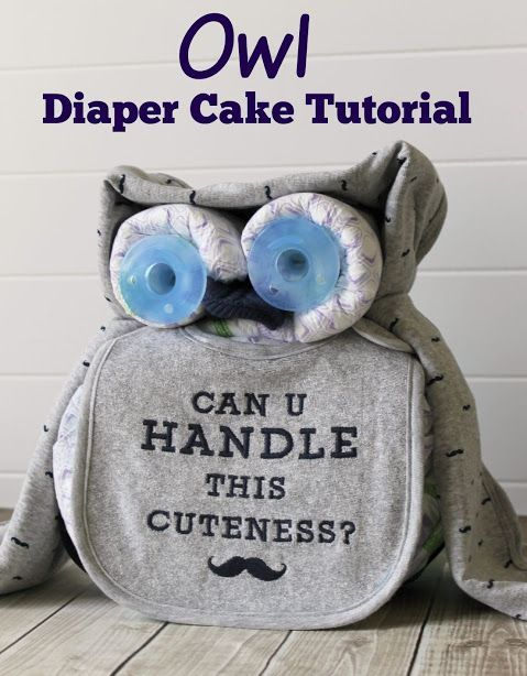 Owl Diaper Cake Tutorial - This sweet owl diaper cake makes a cute baby shower centerpiece. A bib, receiving blanket, some diapers, two binkies, and a knit bootie are all the supplies you need. The mustache print is perfect for a boy, but you could easily change it out for a girl, too!
