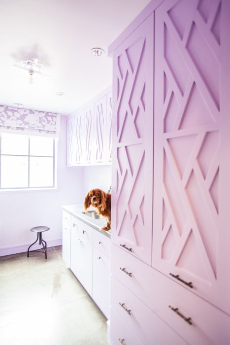 Pink laundry room features pink fretwork cabinets alongside stainless steel countertops.