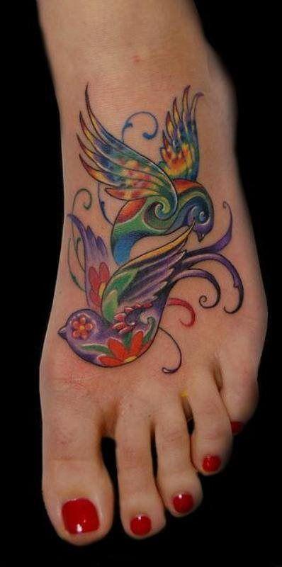 Deux hirondelles multi colore tatouées sur le pied