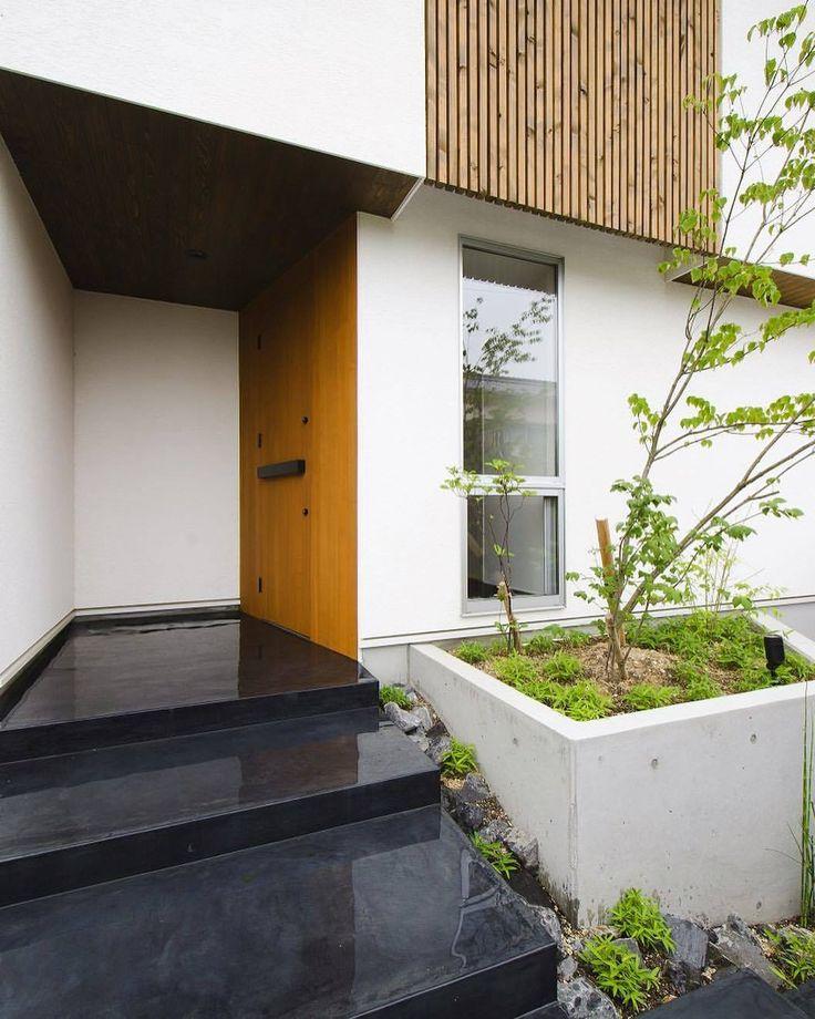 墨モルタルの玄関ポーチ。濡れ色の墨モルタルは表情がある透き通った黒?表現が難しいけどきれいです。白壁と木製ドアと黒モルタルと植栽。 #墨モルタル #玄関 #ポーチ #造作ドア #植栽 #板貼り #ルーバー #格子 #木 #作庭 #塗壁 #白壁 #左官壁 #設計事務所 #設計士とつくる #デザイナーズ住宅 #デザイン住宅 #コラボハウス #香川 #愛媛