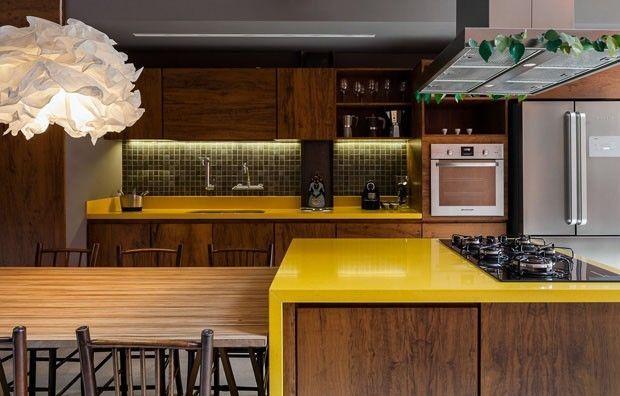 Aqui, a marcenaria de madeira faz par com bancadas amarelas, o que traz um toque de contemporaneidade ao ambiente. O piso de cimento queimado e os eletrodomésticos de aço inox também contribuem para isso. Presente na mesa e nas cadeiras, a madeira faz bonito em ao menos três tipos de tonalidades. Projeto dos arquitetos Chantal e Tito Ficarelli, do escritório Arkitito.
