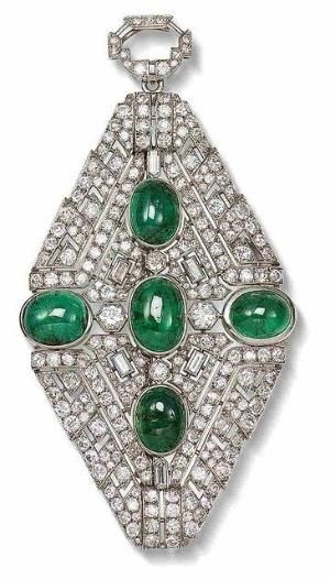 An art deco emerald and diamond brooch/pendant, circa 1930. The openwork plaque set throughout with old brilliant, single and baguette-cut diamonds surrounding five collet-set cabochon emeralds, to a diamond-set surmount, diamonds approximately 11.50 carats total, French assay marks, length 10.3cm.