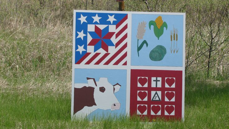 Barn quilt located at 1895 Road 2500 (1 mile west and 2 miles south) Lawrence, NE at the farm of Joe and Frances Brockman. The squares represent our GREAT United States of America; the crops that we raise: milo, corn, wheat and alfalfa; Polled Hereford cattle and the LOVE between us (Joe and Frances) and God.