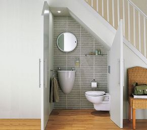 Here is a good example of a modern bathroom below a staircase. Notice the wall mounted sink, which is a great choice because it takes up very very little space.