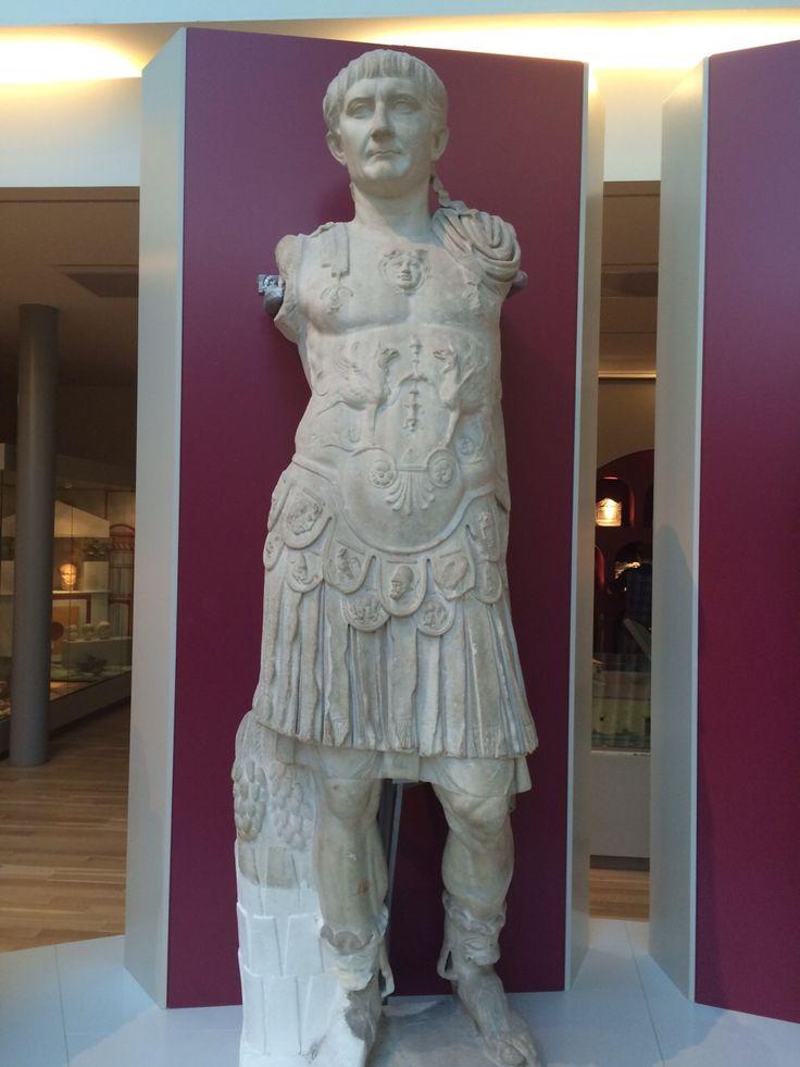 Trajanus was een van de bekendste en succesvolste Romeinse keizers. Dit standbeeld toont hem als machtige generaal en beschermer van het rijk. Onder het borstkuras zijn Remus en Romulus te zien, de stichters van Rome.