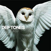 "A snowy owl is shown with its wings open in front of a black background. On the complete left-side of the boarder, the words ""Deftones"" and ""Diamond Eyes"" are shown."