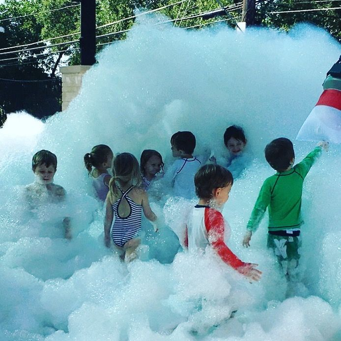 Kids line up to play in the foam machine bubbles. The foam powder packs make the foam machine work wonderfully.