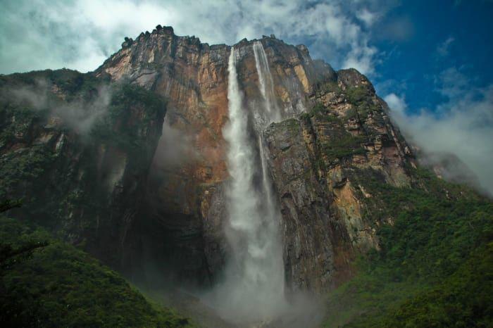 """El Salto Angel e encuentra ubicado en el Parque Nacional Canaima en el Estado Bolívar. Es el salto más alto del mundo, quince veces más alto que las cataratas del Niágara. La montaña desde donde nace y se precipita se conoce como """"El Auyantepuy"""" y es una gigantesca meseta plana (Tepuy).Ganó fama en 1937, después de que el aviador y aventurero estadounidense James C. Ángel (de quien recibe el nombre) aterrizó sobre el Auyantepuy en busca de supuesto oro en la cima de la montaña."""