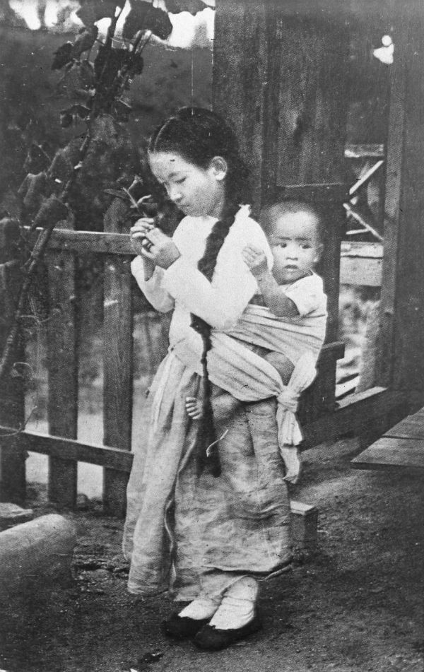 A young girl stands with a baby strapped on her back.
