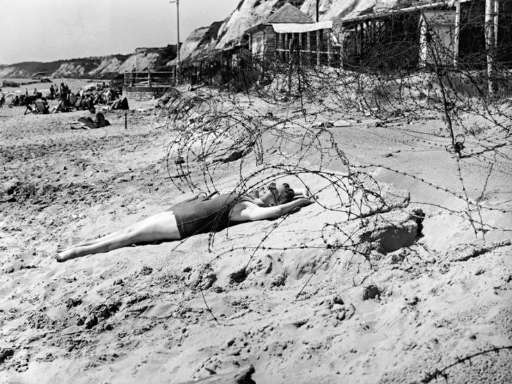A woman sunbathes on a beach in Bournemouth, England among the barbed wire defenses (August 1944)