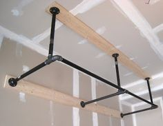 """Snapshots of Bryan: DIY Pull-Up Bar 1"""" black steel pipe and 2""""x6"""" boards. . . had my doubts about 12 screws holding up my body weight, but it feels incredibly solid.  I've jerked and yanked at it and it just doesn't budge.  It's 2' from the ceiling, 2.5' from the wall and 7' in total width. . .cost between $150 and $200. . . more than I was hoping to spend but well worth it for the final result."""