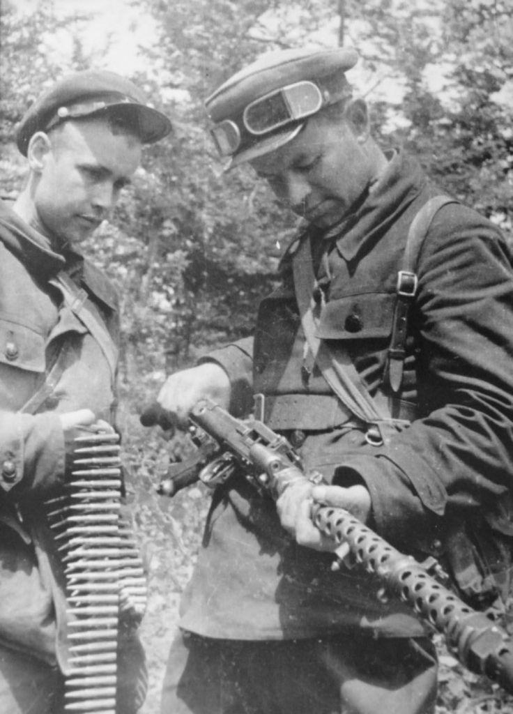 Два советских партизана осматривают трофейный немецкий пулемет MG-34