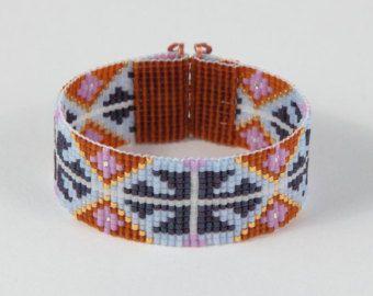 J'ai ce bracelet Inca indien zig-zag sur un métier à tisser à Albuquerque, Nouveau-Mexique de perles. Le design est inspiré par un motif Inca antique et est fait de haute qualité japonaise Delica perles en verre de couleurs vives, audacieuses et irisés: rose, orange, jaune, vert et de robin oeuf bleu. Le fermoir est conçu en cuivre repoussé à la main et est aussi joli que c'est sûr. Ce bracelet mesure 6 3/4 pouces de long par 1 pouce de large.  Remarque importante : Ce bracelet mesure e...