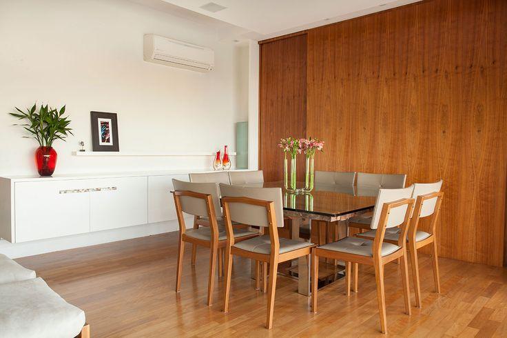 Decoração de apartamento com ambientes integrados e varanda. Na sala de jantar cadeiras de madeira e mesa com tampo de vidro.