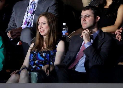 Chelsea Clinton, daughter of Democratic Presidential candidate Hillary Clinton, left, watches alongside her husband Marc Mezvinsky as her father speaks during the second day session of the Democratic National Convention in Philadelphia, Tuesday, July 26, 2016. (AP Photo/Matt Rourke)