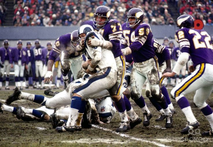 Minnesota Vikings defensive tackle Gary Larsen (77) tackles Los Angeles Rams running back Larry Smith during the 1969 NFL Conference Championship game at Metropolitan Stadium in which the The Vikings defeated the Rams 23-20. Teammates and fellow Purple People Eaters, defensive end Jim Marshall and defensive tackle Alan Page are near by, as well as linebacker Lonnie Warwick and safety Paul Krause.