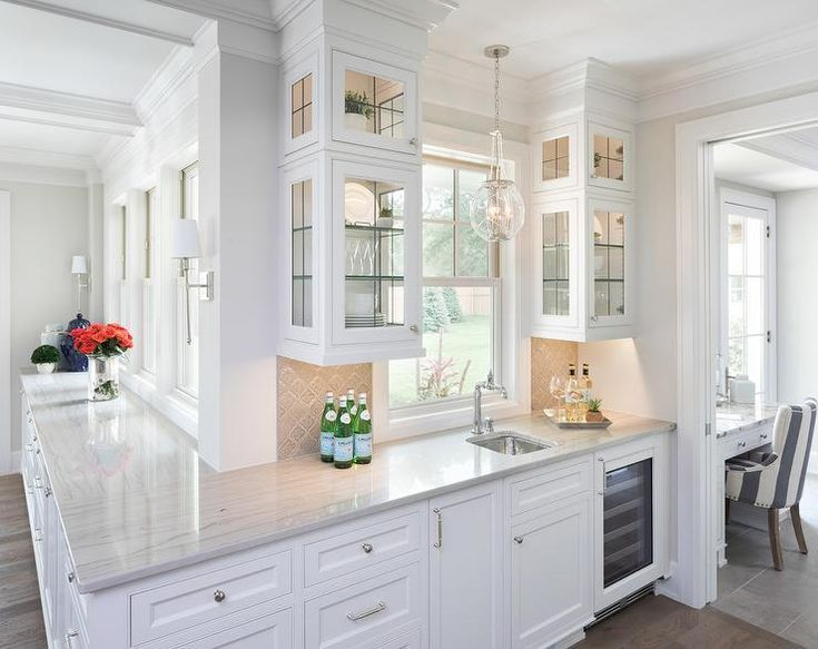 Stacked lighted glass front cabinets with glass shelves flank a window lit by a clear glass globe sconce hung over a small stainless steel prep sink paired with a polished nickel faucet mounted to a white and gray quartzite countertop.