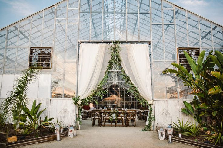 Rustic Greenhouse Wedding on Organic Farm.  Photography by Molly Magee.  Design by Tyler Speier Events. Reception Entrance - fabric with eucalyptus garlands and candles and lanterns